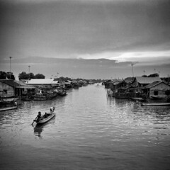 Floating fishing village (MF Pro400H) (Harald Philipp) Tags: clouds moody vacation tourism exotic destination travel adventure wanderlust mysterious atmosphere haraldphilipp outdoors rural blackandwhite bw blackwhite monochrome schwarzweiss nocolor dark shadows contrast fuji pro400h film grain analog filmphotography mediumformat 120film primelens rangefinder fujifilm gf670 cambodia siemreap tonlesap village floatingvillage boat fishingvillage 6x6