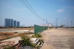. (Out to Lunch) Tags: thu thiem district 2 saigon ho chi minh city vietnam suburban urban road construction pavement fence green blue sky highrises development empty space fuji xt1 2814