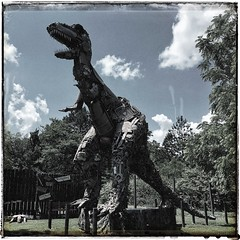 The Beast - Junkosaurus Wrecks | Fischer Crossroads | Fort Payne, Alabama | View 4 (steveartist) Tags: sculpture folkartsculpture trex junkosauruswrecks thebarnyard monumentalart art iphonese snapseed mikegoggans photostevefrenkel dinosaurs outsiderart fischercrossroad fortpayneal trees fence signs sky clouds