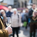 Man holding a glass of white wine, people in the blurry background