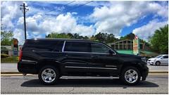Black Suburban SUV, or is it a Suburban Hearse? (steveartist) Tags: cars suvs chevrolets chevroletsuburban road clouds buildings iphonese snapseed photobystevefrenkel blackautomobiles trees