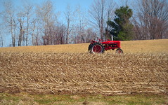 Almost planting time in the U.P> (yooperann) Tags: red farmall tractor stubble field sunny day marquette upper peninsula michigan