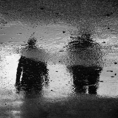 in dreams, I never walk alone (bluechameleon) Tags: sharonwish blackandwhite bluechameleonphotography melancholic moody people puddle reflections seawall square squarecrop street textures vancouver