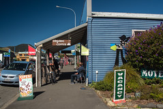 Great Day to be Seating Outside (Jocey K) Tags: marlboroughsounds newzealand southisland marlborough havelock road street cars signs cafe sky hills flowers shadows artwork buildings architecture