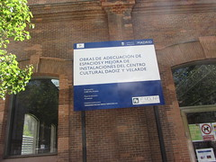 The Work Continues, Cultural Centre  Daoiz and Velarde, Pacífico, Madrid (d.kevan) Tags: pacifico madrid culturalcentredaoizandvelarde sign information publicworks building brick windows plants trees reflections words text figures dates 66