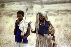 77-286 (ndpa / s. lundeen, archivist) Tags: nick dewolf color photograph photographbynickdewolf 1976 1970s film 35mm 77 reel77 africa northernafrica northeastafrica african ethiopia ethiopian centralethiopia southwesternethiopia people localpeople woman youngwoman man youngman weapon spear necklace necklaces grass grassy landscape terrain headcovering bag sack burlapsack