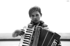 the unsmiling musician (dim.pagiantzas | photography) Tags: people person man boy teen male portrait highlights musician street gipsy environment bokeh look eyes grayscale monochrome absoluteblackandwhite