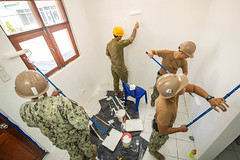 U.S. Navy Seabees and a Royal Australian Army engineer paint the walls of the maternity ward at Vera Cruz Health Clinic during a renovation project.