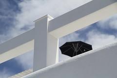 The Black Umbrella (mirella cotella) Tags: holidays sun sky colors tones places travel island santorini greece black blue umbrella white fence