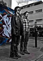 A Couple of likely Lads. (Neil. Moralee) Tags: neilmoralee tauntonsomersetneilmoralee man men two couple young street candid taunton somerset uk graffiti road crossing waiting standing colour spot bw black white blackandwhite sunglasses sunnies leather coat neil moralee olympus omd em5 lpov low point view likely lads boys people urban art