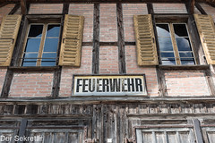Hier ist die Feuerwehr --- This is the fire department (der Sekretär) Tags: backsteine eigenschaften fachwerk fassade fenster fensterladen feuerwehr gebäude haus mauerwerk organisationen schrift schriftzug stein steine tor tür ziegel ziegelsteine abgeblättert abgebröckelt alt brick bricks bröcklig building door facade façade firebrigade firedepartment front gate halftimbered halftimbering house old stone verwittert wall weatherbeaten weathered window windowshutter windows writing holz wood