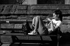 Eye Contact (Silver Machine) Tags: oxford oxfordshire streetphotography street candid streetportrait girl phone mobilephone sitting lying bench mono monochrome blackwhite bw fujifilm fujifilmxt10 fujinonxf35mmf2rwr