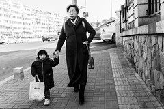 Her duty (Go-tea 郭天) Tags: qingdao shandong républiquepopulairedechine old lady woman young girl family love together 2 grandma grandmother granny child lovely youth duty alone lonely sidewalk pavement lines sun sunny shadow cold winter tilted bag water bottle hat holding hands walk walking wall street urban city outside outdoor people candid bw bnw black white blackwhite blackandwhite monochrome naturallight natural light asia asian china chinese canon eos 100d 24mm prime portrait generation care careness