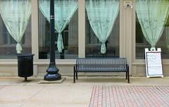 Torn Curtains (Robert Saucier) Tags: berkshires pittsfield rue street façade vitrine vitre glass cristal rideaux curtains banc bench poubelle trashcan lampadaire lampost bancpublic trottoir sidewalk pavement vert green img5916
