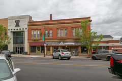Building — Napoleon, Ohio (Pythaglio) Tags: building structure historic napoleon ohio unitedstatesofamerica commercial henrycounty twostory brick classicalrevival orielwindows entablature colorful quoins splayed lintels storefronts altered cars street sidewalk clouds trees