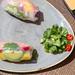 Nahaufnahme von Rainbow Sommerrollen mit Avocado, Mango, Paprika, Rotkohl, Karotten und Reisnudeln serviert mit Koriander und bunten Saucen
