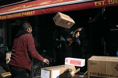 Joyful (markfly1) Tags: soho london chinatown men working stacking throwing boxes red yellow maroon gold golden colour color jackets eye contact full smile happy smiling funny flying box street image streetphoto candid photography cardboard beige nikon d750 35mm manual focus lens