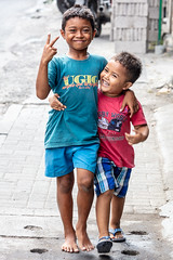 He ain't heavy, he's my brother. (A Different Perspective) Tags: 2 bali jlrayasemer kerobokan blue boy finger path pavement red smile stree