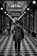 Le tube de l'été (Mathieu HENON) Tags: leica leicam noctilux 50mm m240 monochrome laphotodulundi nb bw bnw noirblanc blackwhite street streetphoto streetlife photoderue france paris 1ier arrondissement galerie passage galerievérododat casque musique couloir damier homme tube cadeau surprise
