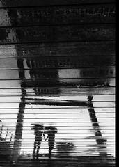 F_MG_1192-BW-1-Canon 6DII-Canon 16-35mm-May Lee 廖藹淳 (May-margy) Tags: maymargy bw 黑白 人像 逆光 剪影 下雨 水灘 倒影 木作步道 木架 幾何構圖 點人 台灣攝影師 模糊 散景 台東縣 台灣 中華民國 街拍 線條造型與光影 天馬行空鏡頭的異想世界 心象意象與影像 雨傘 fmg1192bw1 portrait boardwalk raining umbrella canopy puddle reflection blur bokeh taiwanphotographer taitungcounty taiwan repofchina canon6dii canon1635mm maylee廖藹淳 streetviewphotography mylensandmyimagination linesformsandlightandshadow naturalcoincidencethrumylens humaningeometry humanelement