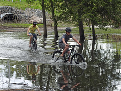 Two young lads joyfully biking through the overwhelmed creek next to the Crystal Beach Wastewater Pumping Station in Nepean (Ottawa), Ontario (Ullysses) Tags: crystalbeachwastewaterpumpingstation nepean ottawa ontario canada spring printemps crystalbeach flooding flood inondation springthaw ottawariverfloodof2019 bicycling youngsters candidphotography candid brittania