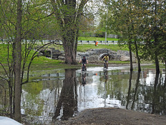 Two young lads joyfully biking through the overwhelmed creek next to the Crystal Beach Wastewater Pumping Station in Nepean (Ottawa), Ontario (Ullysses) Tags: crystalbeachwastewaterpumpingstation nepean ottawa ontario canada spring printemps crystalbeach flooding flood inondation springthaw ottawariverfloodof2019 bicycling youngsters candidphotography candid reflections brittania