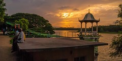 Resting after a walk around the lake. (Bhuvan N) Tags: sunset india mysore mysuru karnataka lake water people street streetphotography orange sunlight beautiful evening talking nikon nikond60 tamron travel indiatravel clouds