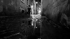 Take a walk on the dark side... (Michael Kalognomos) Tags: rome italy nightlights night rain water reflection alley path ef1635f4lisusm canoneos5dmarkiii canon streetlife streetphotography depthoffield bokeh dof blackwhite bw woman urbanlandscape mirror absoluteblackandwhite