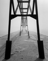 Stranger coming out of the Fog (mswan777) Tags: fog mist weather pier walk person outdoor pattern shape st joseph michigan lighthouse apple iphone iphoneography mobile monochrome ansel black white seascape structure supports