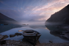 The song of sunrise (Maurizio Fecchio) Tags: sunrise morning sky clouds landscape lake boats fog atmosphere longexposure nopeople lights nature paesaggio alba reflections mountains nikon d7100 travel tranquility haidafilters
