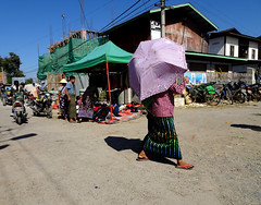 In the centre of Nyaungshwe, Myanmar (Claire Backhouse) Tags: nyaungshwe myanmar burma burmese woman asia asian women walking city citycentre urban bluesky life living ordinary everyday umbrella sunny sun