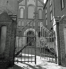 Gate to the Churchyard 21.4.2019 (rieblinga) Tags: berlin neukölln tor zum kirchhof kreuz metall kopfsteinpflaster 2142019 analog rollei 6008 ilford fp4 adox rodinal 150 sw