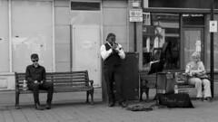 Captive Audience (Crisp-13) Tags: salisbury high street bench busker busking black white monochrome candid people trumpet lady boy