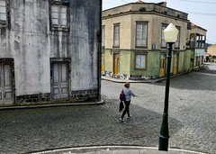 Traffic free (halifaxlight) Tags: portugal azores saomiguel mosteiros street buildings lamp woman walking deserted architecture town intersection windows doors cobblestones