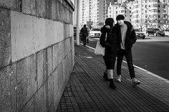 Looking through the eyes of love (Go-tea 郭天) Tags: qingdao shandong républiquepopulairedechine couple young man woman lady love together eyes walk walking sidewalk 2 pair cold winter sun sunny shadow pavement wall lines happy glasses bag movement feeling street urban city outside outdoor people candid bw bnw black white blackwhite blackandwhite monochrome naturallight natural light asia asian china chinese canon eos 100d 24mm prime