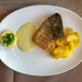 Top View of a grilled salmon fish fillet with herb dip, potato wedges and a lemon slice
