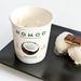 Laktosefreies und pflanzliches Kokosnusseis von Nomoo für vegane Ernährung mit Ritter Sport Schokolade auf einem schwarzen Tablett