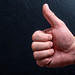 Man's hand showing thumb up - like sign on black background. Concept positive assent