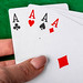 Four aces in a woman's hand on a green background. Playing cards concept