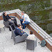 Participants of the Barcamp OMWest relaxing on rattan chairs on a veranda by the lake of the AXA building in Cologne, Germany