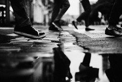 Trampled underfoot (ewitsoe) Tags: puddle street feet crossing walking herd commuters reflection rain water urban citylife city poznan poland erikwitsoe ewitsoe nikon 35mm monochrome bnw blackandwhite