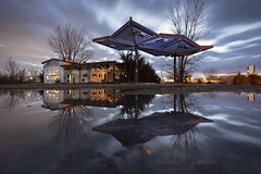 Gas Station Reflection (Notley Hawkins) Tags: clouds cloudy sky cloudysky abandoned kingdomcity callawaycounty notley notleyhawkins 10thavenue gasstation stationdegaz distributoredibenzina postodegasolina gasolinera missouri httpwwwnotleyhawkinscom missouriphotography notleyhawkinsphotography ruralphotography tree awning dusk building architecture entropy 2019 winter puddle lightpaint lightpainting warmcool bluehour thebluehour twilight february quantumflash quantumtrio