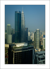 KL skyline (G. Postlethwaite esq.) Tags: borneo fujx100t kl kualalumpur malaysia petronastowers singapore southeastasia unlimitedphotos buildings dusk photoborder sky skyline