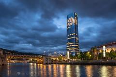 La torre y la ría de Bilbao (Juan Ig. Llana) Tags: bilbao bizkaia vizcaya euskadi españa es ciudad torreiberdrola horaazul cielo nubes tormenta edificio arquitectura río ría agua reflejo explore