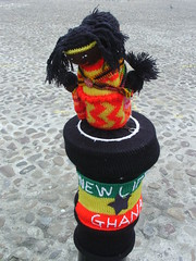 Thirsk knitted helpers New Life Ghana (Nekoglyph) Tags: thirsk yorkshire knitted yarnbombers yarnbombing wool colourful helpers community marketplace cobbles celebration town local newlife ghana flag orange yellow black green star