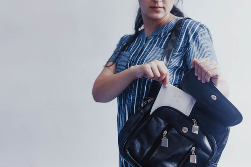 Woman taking sanitary napkins from her bag