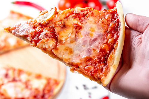 A slice of pizza in hand close-up