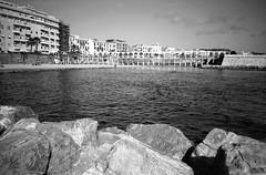 Civitavecchia, il Pirgo (Mattia Camellini) Tags: olympusxa rangefinder pellicola analog canoscan9000fmarkii mattiacamellini civitavecchia italia analogue 35mm biancoenero blackandwithe bn bw rolleiretro80s ilfosol3 panorama mare sea spiaggia pirgo lazio