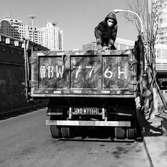 Working with a mask (Go-tea 郭天) Tags: qingdao shandong républiquepopulairedechine truck mask man parked driver work working duty busy cap cold winter sun sunny shadow worker alone lonely dust dirt dirty portrait street urban city outside outdoor people candid bw bnw black white blackwhite blackandwhite monochrome naturallight natural light asia asian china chinese canon eos 100d 24mm prime top
