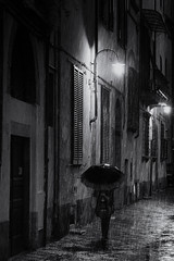 Rainy night - street photography Lucca (www.streetphotography-berlin.com) Tags: rainy rain night woman alone umbrella street streetphotography streetlife walking ally narrow lamps light shadows reflection blackandwhite blackwhite atmospheric moody urban monochrome